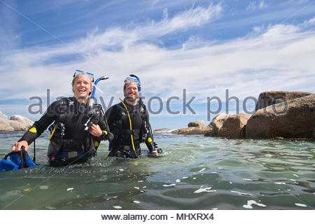 Happy scuba diving couple wading out of ocean after dive - Stock Image