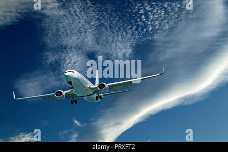 An artistic skyscape view of a commercial passenger jet aircraft flying closeup in a vibrant blue sky, with bright white coloured Cirrocumulus clouds. - Stock Image