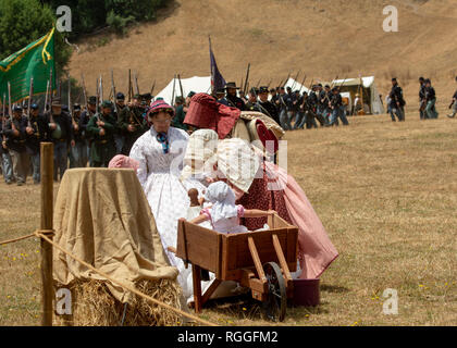 Duncan Mills, CA - July 14, 2018: Union army reenactors behind a country family during a civil war re-enactement. The Civil War Days is one of the lar - Stock Image