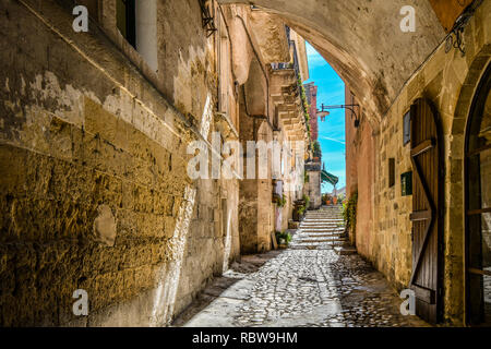 A covered alley leads to a cafe and piazza in the ancient city of Matera, Italy - Stock Image