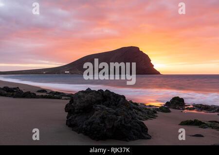 Dawn behind Montana Roja, Red mountain, at Playa de Tejita at sunrise on the east coast of Tenerife, Canary Islands, Spain - Stock Image