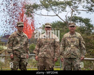 The Hawaii National Guard Joint Task Force 5-0 command team, Col. Neal Mitsuyoshi, Brig. Gen. Kenneth Hara and Col. David Williamson pose in front of a massive lava fountain spewing out from fissure 17 caused by the eruption of the Kilauea volcano May 18, 2018 in Pahoa, Hawaii. - Stock Image