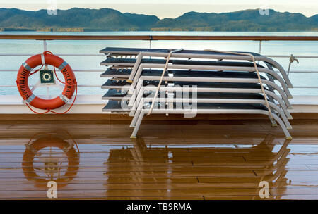 September 17, 2018 - Clarence Strait, AK: Life ring and stacked damp lounge chairs, early morning on deck of cruise ship The Volendam, near Ketchikan. - Stock Image