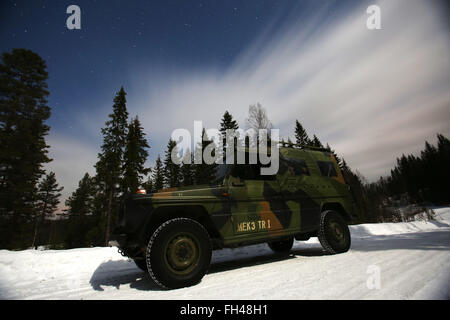 A support vehicle from the Norwegian Telemark Battalion is lit only by the moon on a cold and partially cloudy night. - Stock Image
