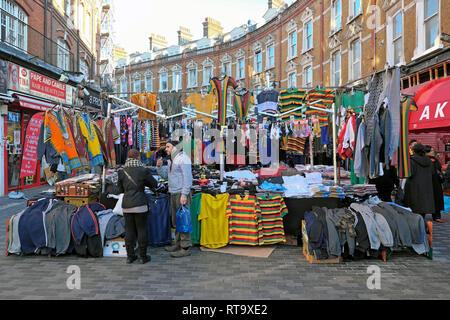 A market trader man selling mens clothing and football shirts in Brixton street market Electric Avenue Brixton South London England UK   KATHY DEWITT - Stock Image