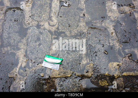 A packet of green Rizla Rolling Papers on wet granite cobblestones on a rainy day - Stock Image