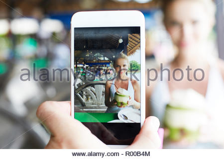 Taking photograph of young woman drinking from coconut - Stock Image