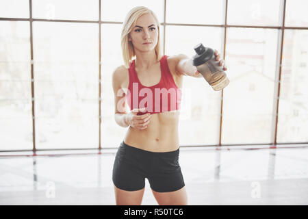 Photo of attractive fitness woman in gym holding bottle of water - Stock Image