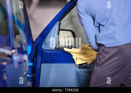Car detailing, man cleaning car with microfiber cloth . - Stock Image