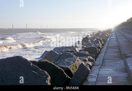 A view of the seawall, rocks, and marker posts on artificial reefs close to shore to protect the coast at Sea Palling, Norfolk, England, UK, Europe. - Stock Image