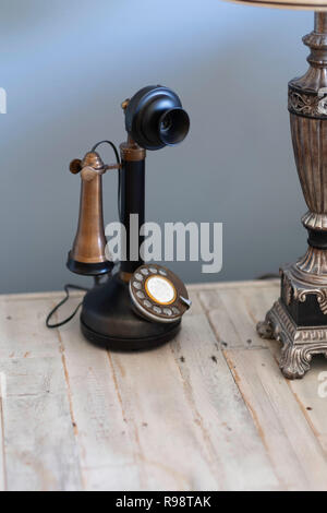 A replica Candlestick telephone, in the popular style of Modern Farmhouse style, set on a rustic wood table indoors. USA. - Stock Image
