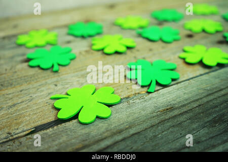 Beautiful close-up of many irish shamrocks, feast clovers, in a row that remind luck or Saint Patrick's Day with bokeh and wooden tables as background - Stock Image