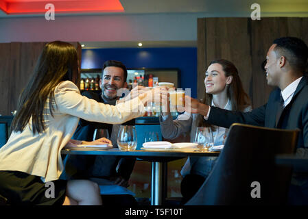 Business people toasting drink at bar - Stock Image