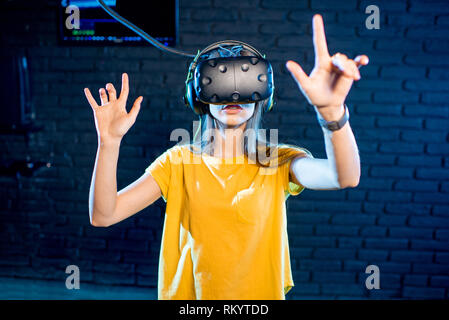 Woman touching virtual reality space using VR headset in the playing room - Stock Image