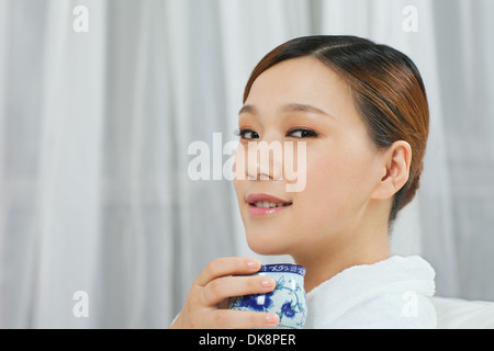 A young woman wearing a bathrobe is drinking tea - Stock Image