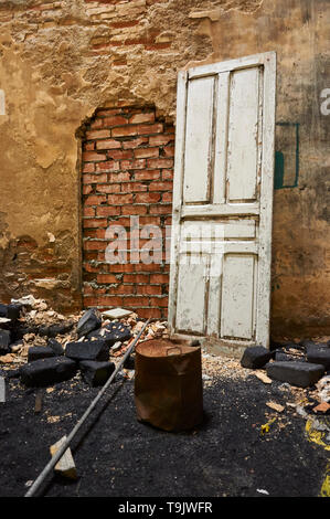 Interior of neglected facilities with wood door and coal bricks at the Canfranc International railway station (Canfranc,Pyrenees,Huesca, Aragon,Spain) - Stock Image
