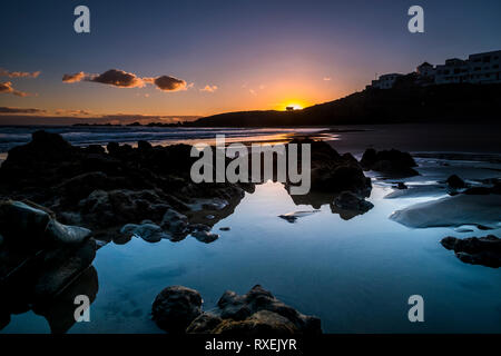 Sunrise or sunset at the ocean beach - beautiful colors and wave and sky - environment and vacation scenery place concept - landscape with coastal cit - Stock Image