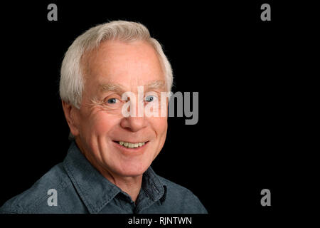 A man in his 60's smiling at the viewer - Stock Image