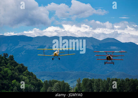 Flying triplane Fokker Dr-1 M and biplane Tiger Moth I-GATO replicas next to each other with mountains in the background. - Stock Image