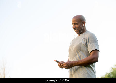 Mature fit African American man listening to music. - Stock Image