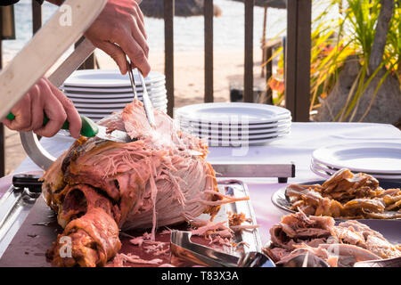 Outdoor celebration with restaurant or catering concept and chef man cutting and serving a tasty nice big turkey - beach in background - Stock Image