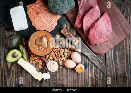 Selection of good fat sources for keto lifestyle. Meat-beef, smoked salmon, eggs, nut butter, nuts, avocado, broccoli, cream cheese, real butter and p - Stock Image