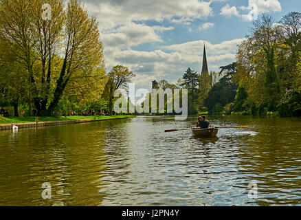 Stratford upon Avon and aAcouple enjoying a trip in a rowing boat on the River Avon, with Holy Trinity church spire - Stock Image