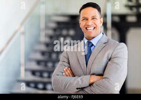 cheerful businessman with arms folded in modern office - Stock Image