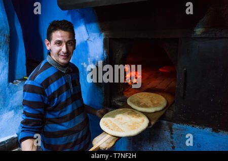Chefchaouen, Morocco : Portrait of man baking flat bread at a traditional oven in the blue-washed medina old town. - Stock Image