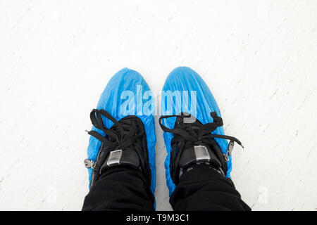 Top view of person`s feet shoes wearing medical antibacterial blue plastic disposable pull on slippers covers in hospital. - Stock Image