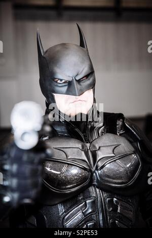A portrait of a male cosplayer wearing a Batman costume and holding a weapon at the camera whilst at a comic con event - Stock Image