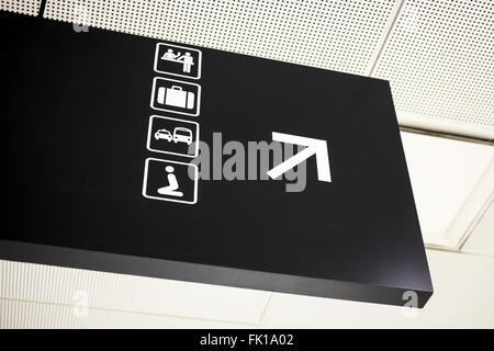 Airport directional arrow sign with symbols for bar, baggage claim, ground transportation, and religious prayer - Stock Image