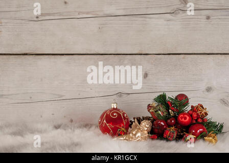 Christmas still life with red glass bauble and ornaments on sheepskin and old wooden background - Stock Image