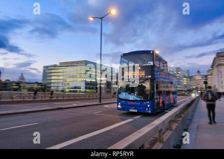 Tour bus moving over London Bridge, London, England, UK - Stock Image