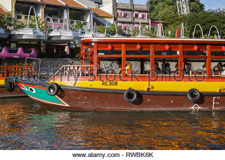 Tourists aboard a river cruise boat at Clarke Quay: Singapore. - Stock Image