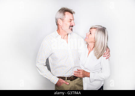 A mature couple posing in a studio arm in arm. - Stock Image