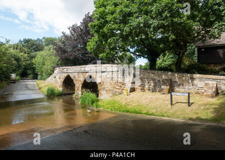 A stone footbridge over a ford in a typical english country village in summertime. Sutton, Bedfordshire - Stock Image