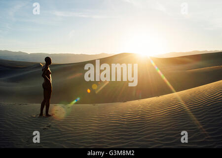 Nude woman in desert on sand dune looking away - Stock Image