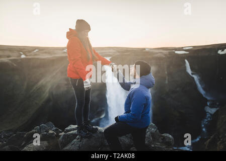 Young man proposing to his girlfriend while hiking by Haifoss waterfall in Iceland - Stock Image