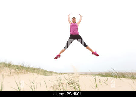 Young woman on the beach. Jump - Stock Image