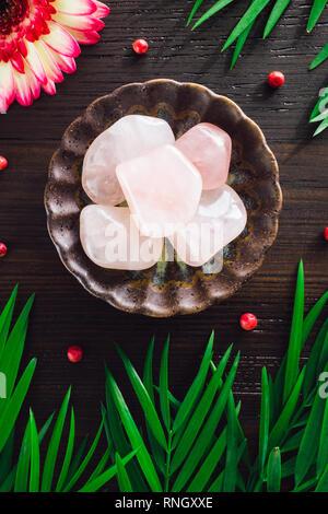 Polished Rose Quartz with Mixed Flora on Dark Wood - Stock Image