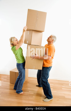 Middle aged couple with stack of cardboard moving boxes. - Stock Image