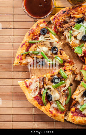 Spicy pizza with chicken gyros, green pepper, olives and onion on cutting board. Top view - Stock Image