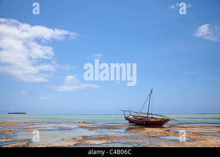 Zanzibar, Matemwe. A boat is stranded on the low tide, with Mnemba Island in the distance. - Stock Image