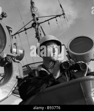 A naval border guard on the deck with binoculars - Stock Image