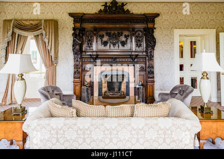 Large oak hearth around the fireplace in a posh sitting room. - Stock Image