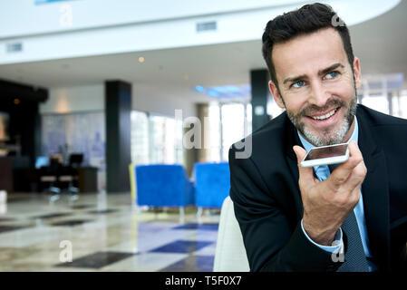 Businessman using smart phone while sitting on sofa - Stock Image