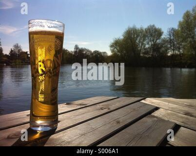 Cool pint of lager beer with a river view. - Stock Image