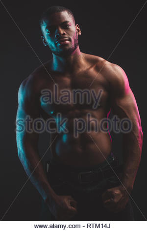 African male athlete with naked torso with six pack posing against dark wall. Low key photo. - Stock Image