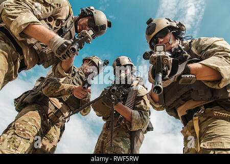 Low angle view of U.S. Army Rangers pointing weapons to the camera. - Stock Image